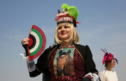 Katharina Dietrich from Germany dressed up with horse designs attends the Dubai World Cup horse race at Meydan Racecourse in Dubai, United Arab Emirates, Saturday, March 29, 2014. Ruler of the World could live up to his name in the $10 million Dubai World Cup when he starts as the 9-2 favorite at the racecourse on Saturday. (AP Photo/Kamran Jebreili)