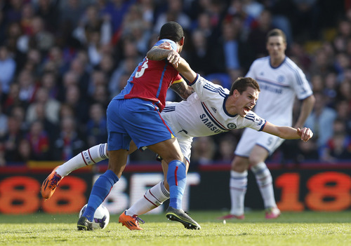 Chelsea's Cesar Azpilicueta, right, is tackled by Crystal Palace's Jason Puncheon during their English Premier League soccer match at Selhurst Park, London, Saturday, March 29, 2014. (AP Photo/Sang Tan)