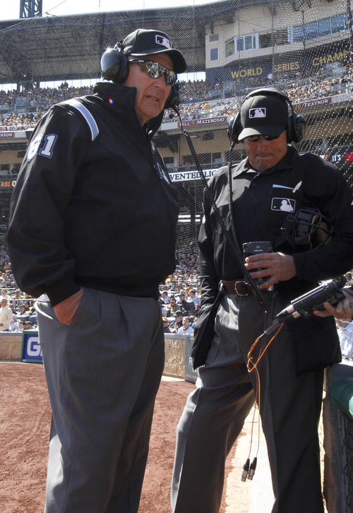 First base umpire Bob Davidson (61) and home plate umpire John Hirschbeck, talk over headsets as a play at first base is being reviewed in the fifth inning during the opening day baseball game between the Pittsburgh Pirates and the Chicago Cubs on Monday, March 31, 2014, in Pittsburgh. Chicago Cubs manager Rick Renteria requested a replay on an out call. (AP Photo/Gene Puskar)
