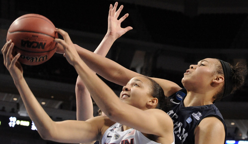 CORRECTS TO CONNECTICUT'S KIAH STOKES INSTEAD OF CONNECTICUT'S STEFANIE DOLSON - Connecticut's Kiah Stokes, left, takes a shot in front of BYU's Morgan Bailey during the second half of a regional semifinal in the NCAA women's college basketball tournament Saturday, March 29, 2014, in Lincoln, Neb. Connecticut won 70-51. (AP Photo/Dave Weaver)
