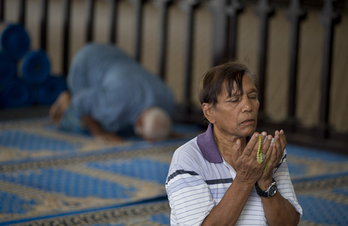 """Muslims pray at a mosque in Yangon, Myanmar, Tuesday, April 1, 2014. Enumerators continued to fan out across Myanmar since Sunday for a census that has been widely criticized for stoking religious and ethnic tensions, after the government denied members of a long-persecuted Muslim minority the right to identify themselves as """"Rohingya."""" (AP Photo/Gemunu Amarasinghe)"""