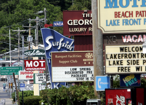 FILE - In this Tuesday, May 26, 2009 photo, motel signs are seen in Lake George, N.Y. Summer vacationers looking for a deal on hotel rooms in 2014 are going to have to search a little harder. The average cost of a room now stands at $110, up 4 percent from last year and 8 from two years ago, according to travel research company STR.  (AP Photo/Mike Groll, File)