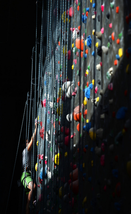 Steve Griffin  |  The Salt Lake Tribune Autumn Schley climbs into a section of wall that is lit by the sun at Momentum indoor climbing gym in Sandy, Utah Wednesday, April 2, 2014.