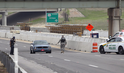 Vehicles are checked outside of the Bernie Beck Gate, Wednesday, April 2, 2014, in Fort Hood, Texas. One person was killed and 14 injured in a shooting at Fort Hood, and officials at the base said the shooter is believed to be dead. (AP Photo/American-Statesman, Deborah Cannon)
