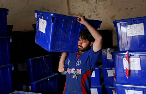 An Afghan election worker carries a ballot box at an election commission office in Jalalabad east of Kabul, Afghanistan, Wednesday, April 2, 2014. Eight Afghan presidential candidates are campaigning for the third presidential election. Elections will take place on April 5, 2014. (AP Photo/Rahmat Gul)
