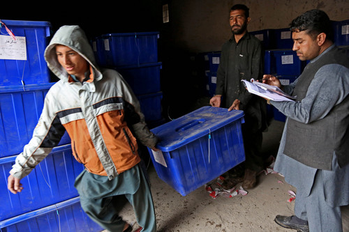 Afghan election workers carry a ballot box at an election commission office in Jalalabad east of Kabul, Afghanistan, Wednesday, April 2, 2014. Eight Afghan presidential candidates are campaigning for the third presidential election. Elections will take place on April 5, 2014. (AP Photo/Rahmat Gul)