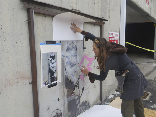 Jay Hamburger | Park Record                                Deborah Uhl, a painting conservator, repairs the Banksy artwork in Park City on March 29, 2014. A vandal damaged the art about Jan. 1, 2014.