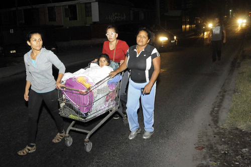 Women push a child in a grocery cart as the evacuate their homes after a strong aftershock in Iquique, Chile, early Thursday, April 3, 2014. A powerful aftershock hit Chile's far-northern coast late Wednesday night, shaking the same area where a magnitude-8.2 earthquake hit just a day before causing some damage and six deaths. (AP Photo/Cristian Vivero) NO PUBLICAR EN CHILE