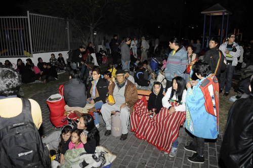 People sit outside as they evacuate their homes after a strong aftershock in Iquique, Chile, early Thursday, April 3, 2014. A powerful aftershock hit Chile's far-northern coast late Wednesday night, shaking the same area where a magnitude-8.2 earthquake hit just a day before causing some damage and six deaths. (AP Photo/Cristian Vivero) NO PUBLICAR EN CHILE