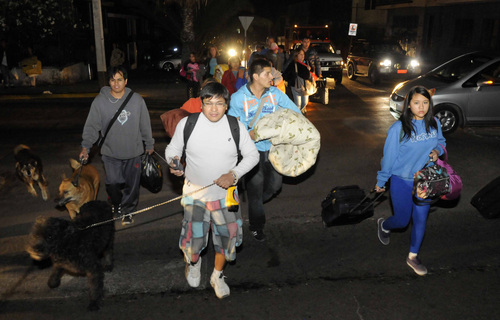 People evacuate their homes after a strong aftershock in Iquique, Chile, early Thursday, April 3, 2014. A powerful 7.8-magnitude aftershock hit Chile's far-northern coast late Wednesday night, shaking the same area where a magnitude-8.2 earthquake hit just a day before causing some damage and six deaths. (AP Photo/Cristian Vivero)