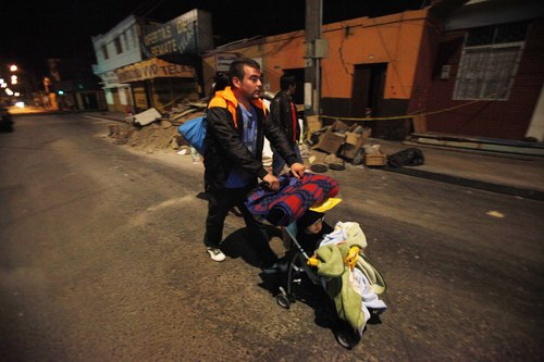 A man pushing a baby leaves his home as he walks to a safe area after a strong aftershock in Arica, Chile, early Thursday, April 3, 2014. A powerful 7.8-magnitude aftershock hit Chile's far-northern coast late Wednesday night, shaking the same area where a magnitude-8.2 earthquake hit just a day before causing some damage and six deaths. (AP Photo/Luis Hidalgo)
