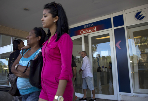 """Customers looking for cellphone service wait their turn to be seen by a representative outside a branch of telecommunications provider Cubacel in Havana, Cuba, Tuesday, April 1, 2014. The Obama administration secretly financed a social network in Cuba to stir political unrest and undermine the country's communist government an Associated Press investigation found. The project, dubbed """"ZunZuneo,"""" slang for a Cuban hummingbird's tweet, evaded Cuba's Internet restrictions by creating a text-messaging service that could be used to organize political demonstrations. Even though Cuba has one of the most sophisticated counter-intelligence operations in the world, the ZunZuneo team thought that as long as the message service looked benign, Cubacel would leave it alone.  (AP Photo/Ramon Espinosa)"""