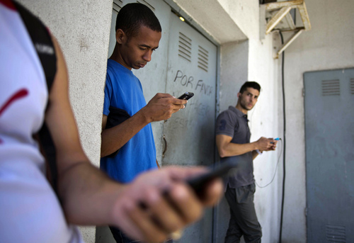 """Students gather behind a business looking for a Internet signal for their smart phones in Havana, Cuba, Tuesday, April 1, 2014.  The U.S. Agency for International Development masterminded the creation of a """"Cuban Twitter,"""" a communications network designed to undermine the communist government in Cuba, built with secret shell companies and financed through foreign banks, The Associated Press has learned. The project, which lasted more than two years and drew tens of thousands of subscribers, sought to evade Cuba's stranglehold on the Internet with a primitive social media platform. Its users were neither aware it was created by a U.S. agency with ties to the State Department, nor that American contractors were gathering personal data about them. In 2012, the text messaging service vanished as mysteriously as it appeared.  (AP Photo/Ramon Espinosa)"""