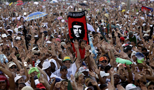 """FILE - In this Sept. 20, 2009 file photo, a person holds a banner with an image of of Argentine-born revolutionary Ernesto """"Che"""" Guevara, among a crowd of cheering fans at the """"Peace Without Borders"""" concert in Revolution square in Havana, Cuba. The U.S. government masterminded the creation of a """"Cuban Twitter""""  a communications network designed to undermine the communist government in Cuba, built with secret shell companies and financed through foreign banks, The Associated Press has learned. The project, dubbed """"ZunZuneo,"""" slang for a Cuban hummingbird's tweet, and for the team, the concert was a perfect opportunity to test the political power of their budding social network. (AP Photo/Javier Galeano, File)"""