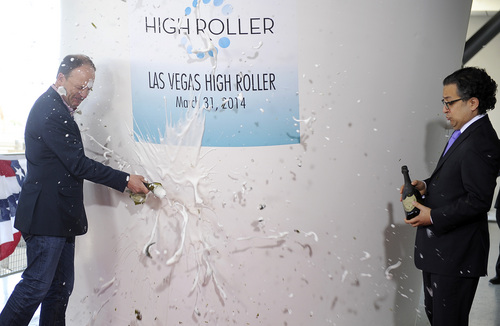 David Codiga, left,  executive project director of The LINQ breaks a bottle of champagne as Tariq Shaukat, chief marketing officer of Caesars Entertainment looks on during the opening of the Las Vegas High Roller at The LINQ on March 31, 2014, in Las Vegas. The 550-foot-tall attraction, which opened to the public today, is the highest observation wheel in the world and features 28 cabins that can accommodate up to 40 people each. (AP Photo/David Becker)