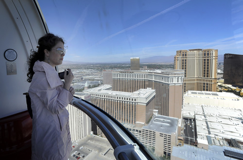 Jen Chase looks out from one of the cabins as she rides the Las Vegas High Roller at The LINQ on Monday, March 31, 2014, in Las Vegas.  The 550-foot-tall attraction, which opened to the public Monday, is the highest observation wheel in the world.  A full revolution takes 30 minutes.   The height tops the nearly 443-foot London Eye and the 541-foot Singapore Flyer. (AP Photo/David Becker)