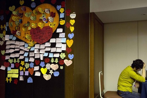 A relative of Chinese passengers onboard the missing Malaysia Airlines MH370 rests near messages of well wishes, pasted onto the wall, in a prayer room in Beijing, China, Thursday, April 3, 2014.  No trace of the Boeing 777 has been found nearly a month after it vanished in the early hours of March 8 on a flight from Kuala Lumpur to Beijing with 239 people on board. (AP Photo/Ng Han Guan)