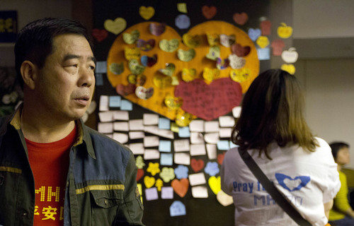 Relatives of Chinese passengers onboard the Malaysia Airlines MH370 stand near messages of well wishes, pasted onto the wall,  in a prayer room in Beijing, China, Thursday, April 3, 2014.  No trace of the Boeing 777 has been found nearly a month after it vanished in the early hours of March 8 on a flight from Kuala Lumpur to Beijing with 239 people on board. (AP Photo/Ng Han Guan)