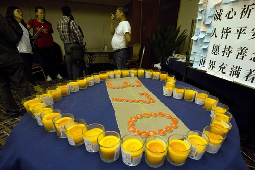 Relatives of Chinese passengers onboard the Malaysia Airlines MH370 stand near candles arranged as a memorial in a prayer room in Beijing, China, Thursday, April 3, 2014.  No trace of the Boeing 777 has been found nearly a month after it vanished in the early hours of March 8 on a flight from Kuala Lumpur to Beijing with 239 people on board. (AP Photo/Ng Han Guan)