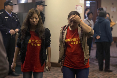 """Relatives of the Chinese passengers onboard the Malaysia Airlines flight MH370 wear T-shirts with the words """"Pray for MH370, safe return"""" in Beijing Thursday, April 3, 2014. No trace of the Boeing 777 has been found nearly a month after it vanished in the early hours of March 8 on a flight from Kuala Lumpur to Beijing with 239 people on board. (AP Photo/Ng Han Guan)"""