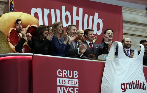 GrubHub CEO Matthew Maloney, third from right, is applauded as he rings the New York Stock Exchange opening bell, Friday, April 4, 2014. Investors sent shares of online food ordering service GrubHub Inc. up 51 percent to $39.20 in early trading in its stock market debut Friday. (AP Photo/Richard Drew)
