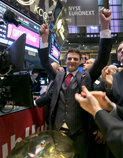 GrubHub CEO Matthew Maloney raises his arms in celebration after ringing a ceremonial bell as his company's IPO begins trading, on the floor of the New York Stock Exchange Friday, April 4, 2014. Investors sent shares of online food ordering service GrubHub Inc. up 51 percent to $39.20 in early trading in its stock market debut Friday. (AP Photo/Richard Drew)