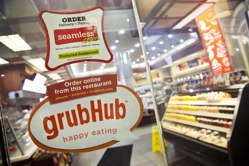 Signs for GrubHub and Seamless are displayed on the door to a New York restaurant, Friday, April 4, 2014. Shares in GrubHub will begin trading at the New York Stock Exchange Friday. GrubHub, based in Chicago, also owns the Seamless food ordering website. The company connects nearly 29,000 restaurants with users in more than 600 U.S. cities. More than 3 million people have placed an order through GrubHub websites in the past year. (AP Photo/Mark Lennihan)