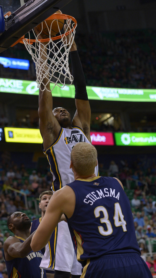 Leah Hogsten  |  The Salt Lake Tribune Utah Jazz center Derrick Favors (15) with a dunk over New Orleans Pelicans center Greg Stiemsma (34). The Utah Jazz defeated the New Orleans Pelicans 100-96 during their game Friday, April 4, 2014 at Energy Solutions Arena.