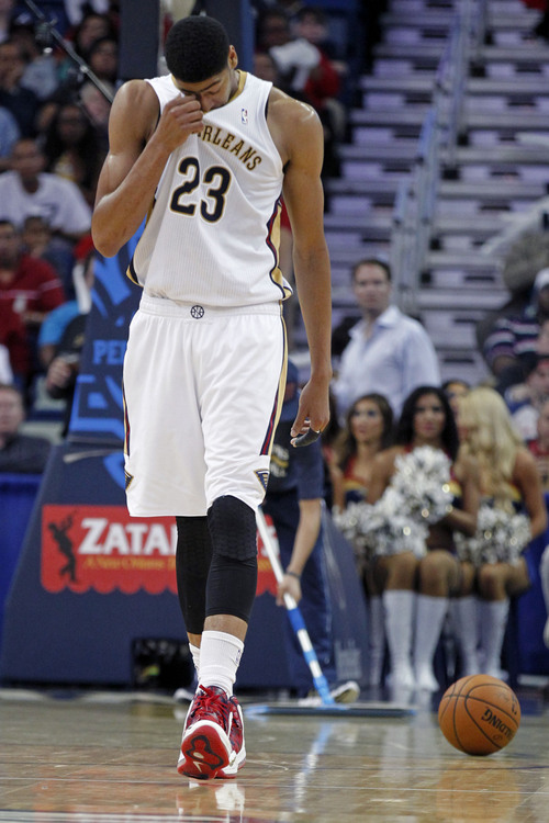 New Orleans Pelicans forward Anthony Davis (23) rubs his eye after being fouled by Sacramento Kings forward Reggie Evans in the second half of an NBA basketball game in New Orleans, Monday, March 31, 2014. Evans was ejected on a flagrant-2 foul on the play. The Kings won 102-97. (AP Photo/Gerald Herbert)