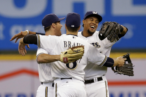 Milwaukee Brewers' Logan Schaffer, left, Ryan Braun and Carlos Gomez react after beating the Atlanta Braves in the Opening day baseball game Monday, March 31, 2014, in Milwaukee. The Brewers won 2-0.  (AP Photo/Jeffrey Phelps)