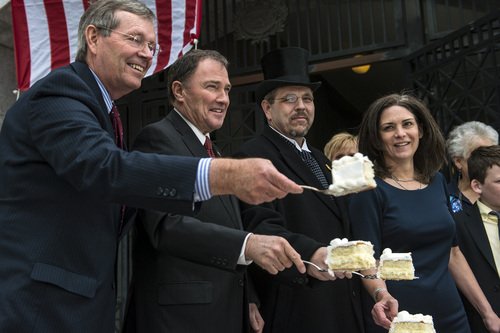 Chris Detrick  |  The Salt Lake Tribune Former Gov. Mike Leavitt,  Gov. Gary Herbert and  Joseph Soderborg (portraying former Gov. William Spry) hold up cake slices during a ceremony marking the 100th anniversary of the laying of the cornerstone of the Utah State Capitol Friday April 4, 2014.