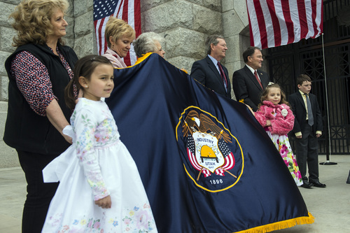 Chris Detrick  |  The Salt Lake Tribune Sophia Molenaar, 6, and Arianna Vasquez, 6, hold a new embroidered Utah State flag -- that will hang in the governor's office--  during a ceremony marking the 100th anniversary of the laying of the cornerstone of the Utah State Capitol, Friday April 4, 2014. Former Gov. Mike Leavitt and Gov. Gary Herbert are in the back right.