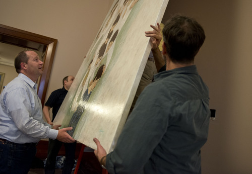Lennie Mahler  |  The Salt Lake Tribune Brian Kershisnik helps hang one of his paintings up on the first floor of the LDS Conference Center with painting owner Cris Baird, left, on Thursday, April 3, 2014.