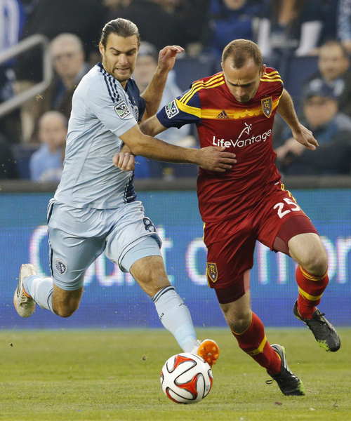 Sporting Kansas City midfielder Graham Zusi, left, and Real Salt Lake defender Rich Balchan (25) race for the ball during the first half of an MLS soccer match in Kansas City, Kan., Saturday, April 5, 2014. (AP Photo/Orlin Wagner)