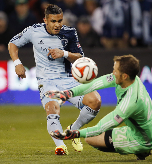 Real Salt Lake goalkeeper Jeff Attinella (24) deflects a kick by Sporting Kansas City forward Dom Dwyer, left, during the first half of an MLS soccer match in Kansas City, Kan., Saturday, April 5, 2014. (AP Photo/Orlin Wagner)