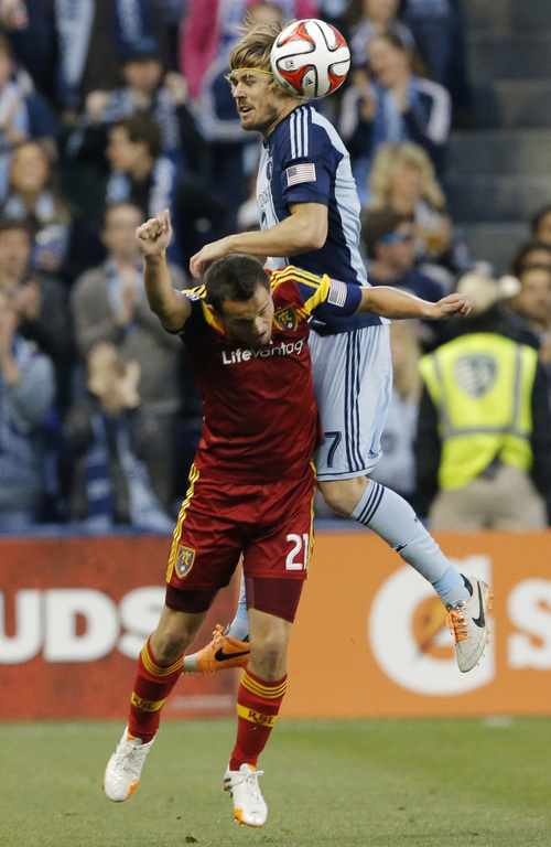 Sporting Kansas City defender Chance Myers (7) heads the ball over Real Salt Lake midfielder Luis Gil (21) during the first half of an MLS soccer match in Kansas City, Kan., Saturday, April 5, 2014. (AP Photo/Orlin Wagner)