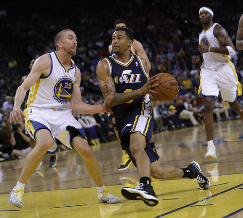 Utah Jazz guard Trey Burke, center, drives to the basket next to Golden State Warriors guard Steve Blake, left, during the second half of an NBA basketball game Sunday, April 6, 2014, in Oakland, Calif. Golden State won 130-102. (AP Photo/Marcio Jose Sanchez)