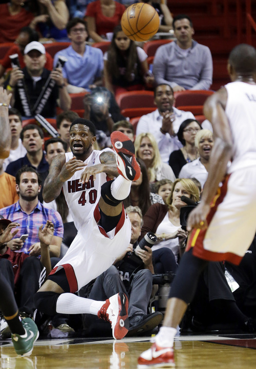 Miami Heat forward Udonis Haslem (40) passes the ball to center Chris Bosh to keep it in bounds during the second half of an NBA basketball game against the New York Knicks, Sunday, April 6, 2014, in Miami. The Heat won 102-91. (AP Photo/Wilfredo Lee)
