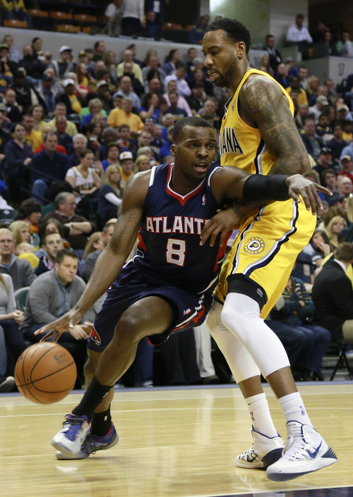 Atlanta Hawks guard Shelvin Mack (8) pushes his way past Indiana Pacers guard Rasual Butler in the first half of an NBA basketball game in Indianapolis, Sunday, April 6, 2014. (AP Photo/R Brent Smith)
