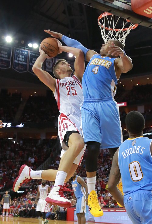 Houston Rockets forward Chandler Parsons goes up for a shot against Denver Nuggets guard Randy Foye during overtime of an NBA basketball game in Houston on Sunday, April 6, 2014. The Rockets won 130-125.  (AP Photo/Richard Carson)
