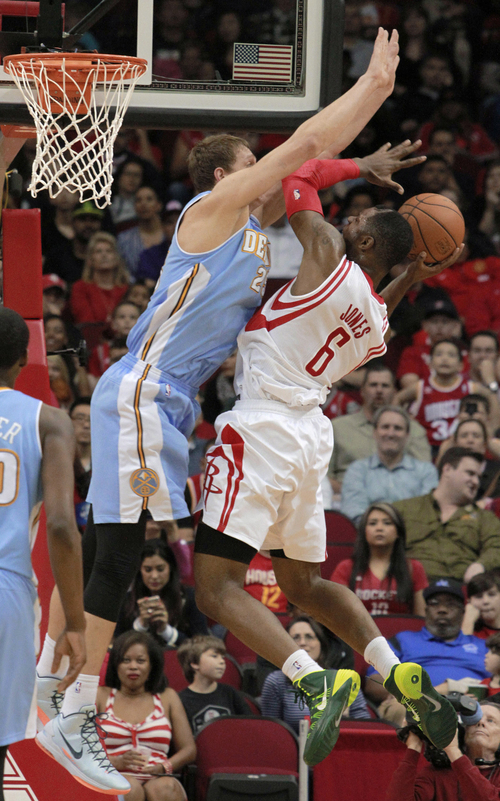 Denver Nuggets center Timofey Mozgov defends as Houston Rockets forward Terrence Jones goes to the basket during the first half of an NBA basketball game in Houston on Sunday, April 6, 2014. (AP Photo/Richard Carson)