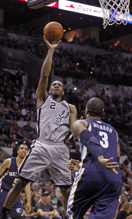San Antonio Spurs' Kawhi Leonard (2) puts up at shot against Memphis Grizzlies'  James Johnson (3) during the second half of an NBA basketball game, Sunday, April 6, 2014, in San Antonio.  (AP Photo/Michael Thomas)