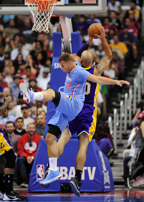 Los Angeles Clippers forward Blake Griffin (32) and Los Angeles Lakers center Robert Sacre, right, fight for a rebound in the first half of an NBA basketball game on Sunday, April 6, 2014, in Los Angeles. (AP Photo/Gus Ruelas)