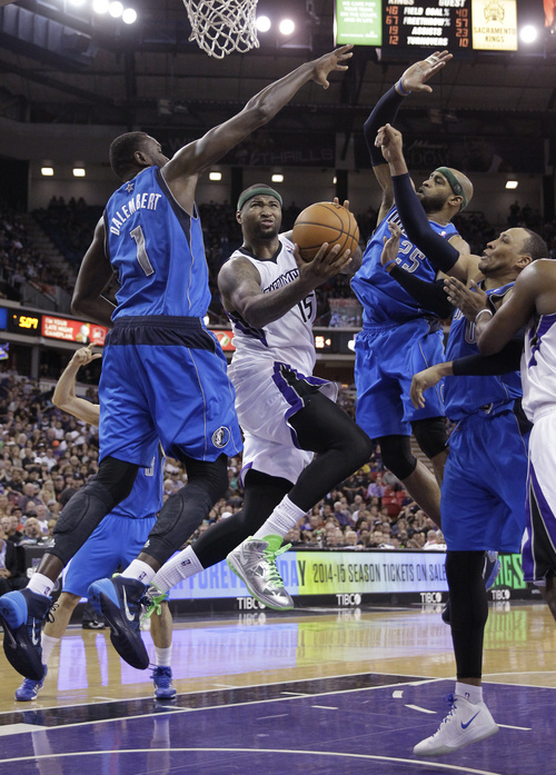 Sacramento Kings center DeMarcus Cousins, center, drives to the basket between Dallas Mavericks' Samuel Dalembert, left; Vince Evans, second from right; and Shawn Marion, right, during the fourth quarter of an NBA basketball game, Sunday, April 6, 2014, in Sacramento, Calif. The Mavericks won 93-91. (AP Photo/Rich Pedroncelli)