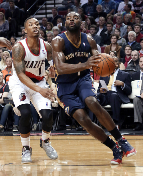 New Orleans Pelicans guard Tyreke Evans, right, drives to the basket past Portland Trail Blazers guard Damian Lillard during the first half of an NBA basketball game in Portland, Ore., Sunday, April 6, 2014. (AP Photo/Don Ryan)