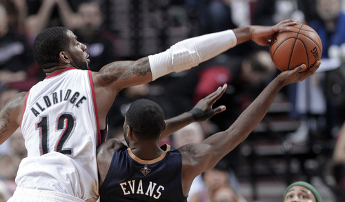 Portland Trail Blazers forward LaMarcus Aldridge, left, blocks a shot by New Orleans Pelicans guard Tyreke Evans during the second half of an NBA basketball game in Portland, Ore., Sunday, April 6, 2014. Aldridge scored 25 points and pulled in 18 rebounds as the Trail Blazers defeated the Pelicans 100-94. (AP Photo/Don Ryan)