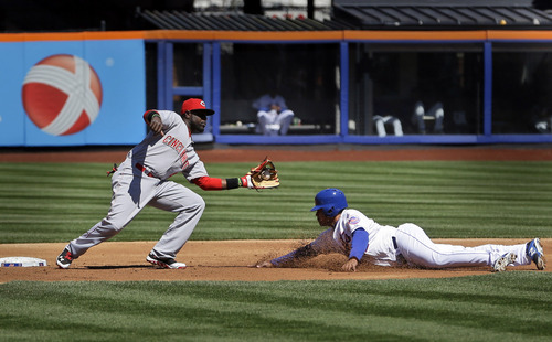 Cincinnati Reds second baseman Brandon Phillips, left, tags out New York Mets' Juan Lagares who was trying to steal second base during the second inning of a baseball game at Citi Field, Sunday, April 6, 2014, in New York. (AP Photo/Seth Wenig)