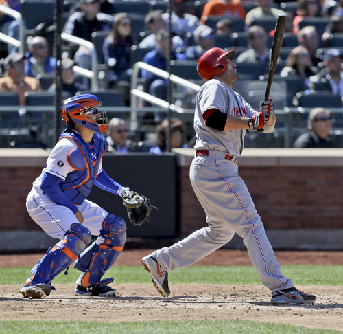 New York Mets catcher Travis d'Arnaud, left, and Cincinnati Reds' Joey Votto watch Votto's sacrifice fly during the sixth inning of a baseball game at Citi Field, Sunday, April 6, 2014, in New York. (AP Photo/Seth Wenig)