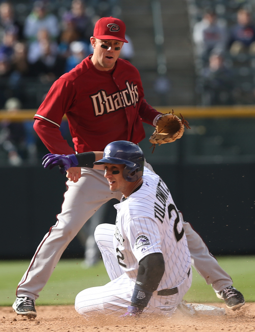 Arizona Diamondbacks second baseman Aaron Hill, back, forces out Colorado Rockies' Troy Tulowitzki at second base on the front end of a double play hit into by Wilin Rosario in the ninth inning of the Diamondbacks' 5-3 victory in a baseball game in Denver on Sunday, April 6, 2014. (AP Photo/David Zalubowski)