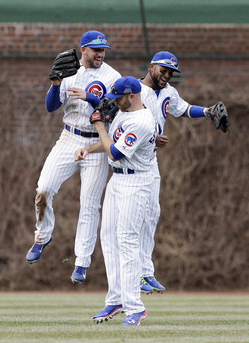 Chicago Cubs left fielder Ryan Kalish, from left, right fielder Nate Schierholtz and center fielder Emilio Bonifacio celebrate after the Cubs defeated the Philadelphia Phillies 8-3 in a baseball game in Chicago, Sunday, April 6, 2014. (AP Photo/Nam Y. Huh)